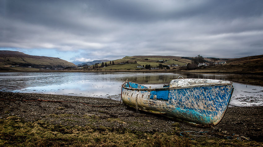 Old blue shipwreck at the coastline on the Isle of Skye in Scotland